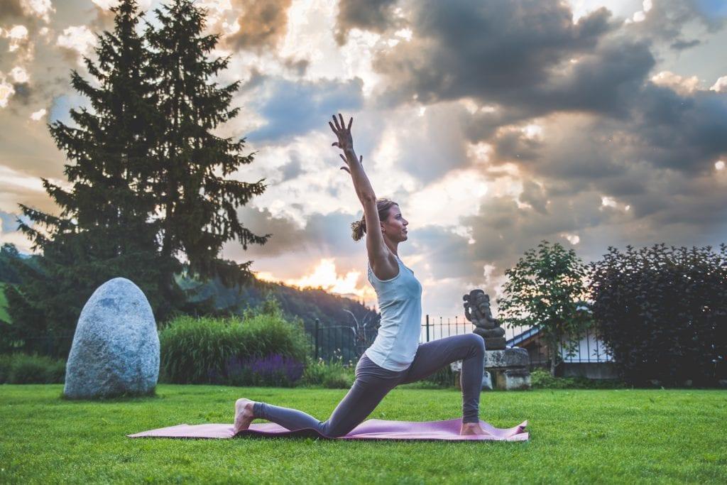 frau macht yogaübung krieger auf lila yogamatte in garten, natur