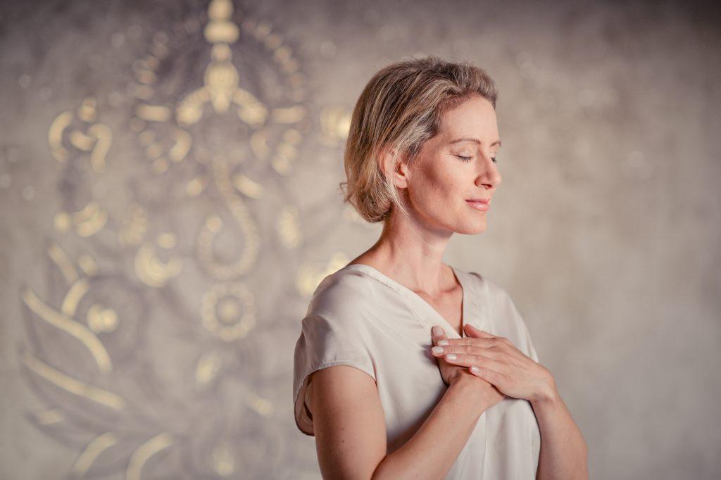 frau legt hände auf das herz, yogapose, meditation