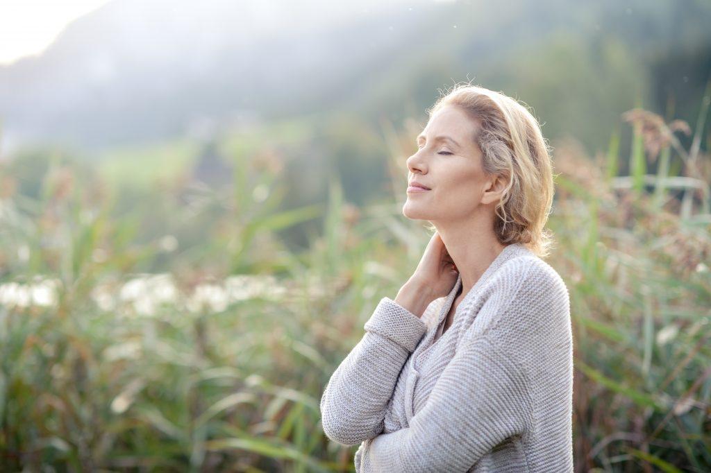 frau mit geschlossenen augen genießt die natur, sonnenschein
