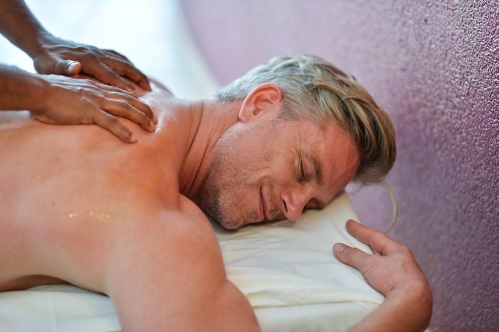 mann bekommt rückenmassage, entspannung, wellnessbereich