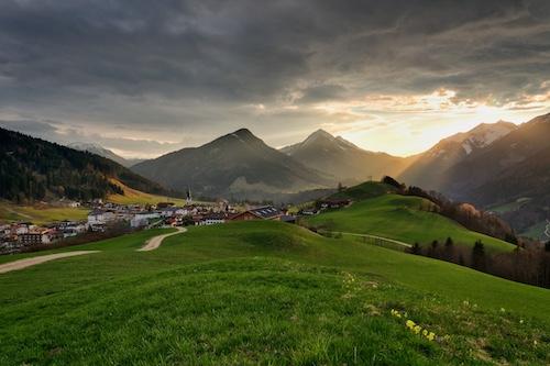 Sonnenschein mit bedecktem Himmel auf einer Wiese in Tirol mit Bergblick
